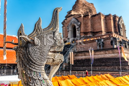 The statue of a dragon stands in front of a temple in the city of Chang Mai