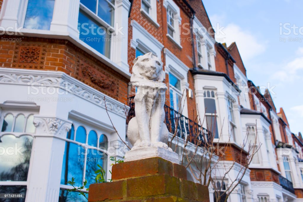 Statue of a lion in white stone in front of a row of restored luxury Victorian houses in red bricks and white finishing on a local street in London, UK stock photo