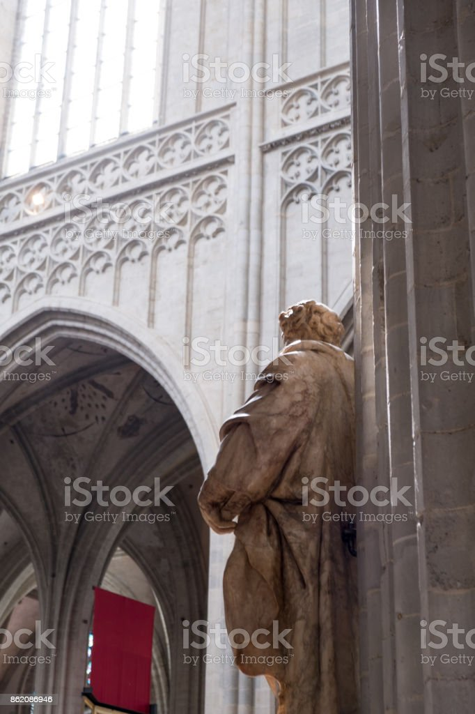 Statue of a saint inside a gothic cathedral in Europe. Pointed arches and groin vault decorated with delicate tracery. Interior of 14th century European cathedral. stock photo