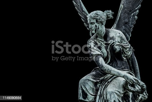 Statue of ancient beautiful winged angel in downtown of Potsdam, isolated at black background, Germany
