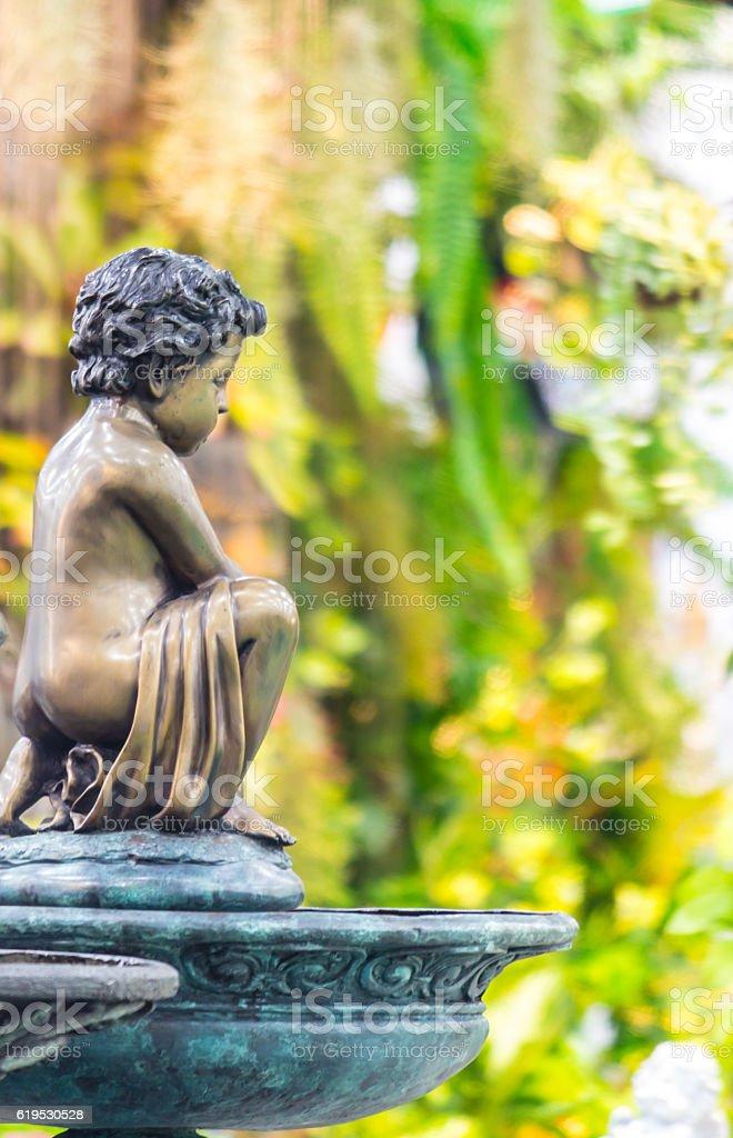 Statue of angel in cozy garden. stock photo