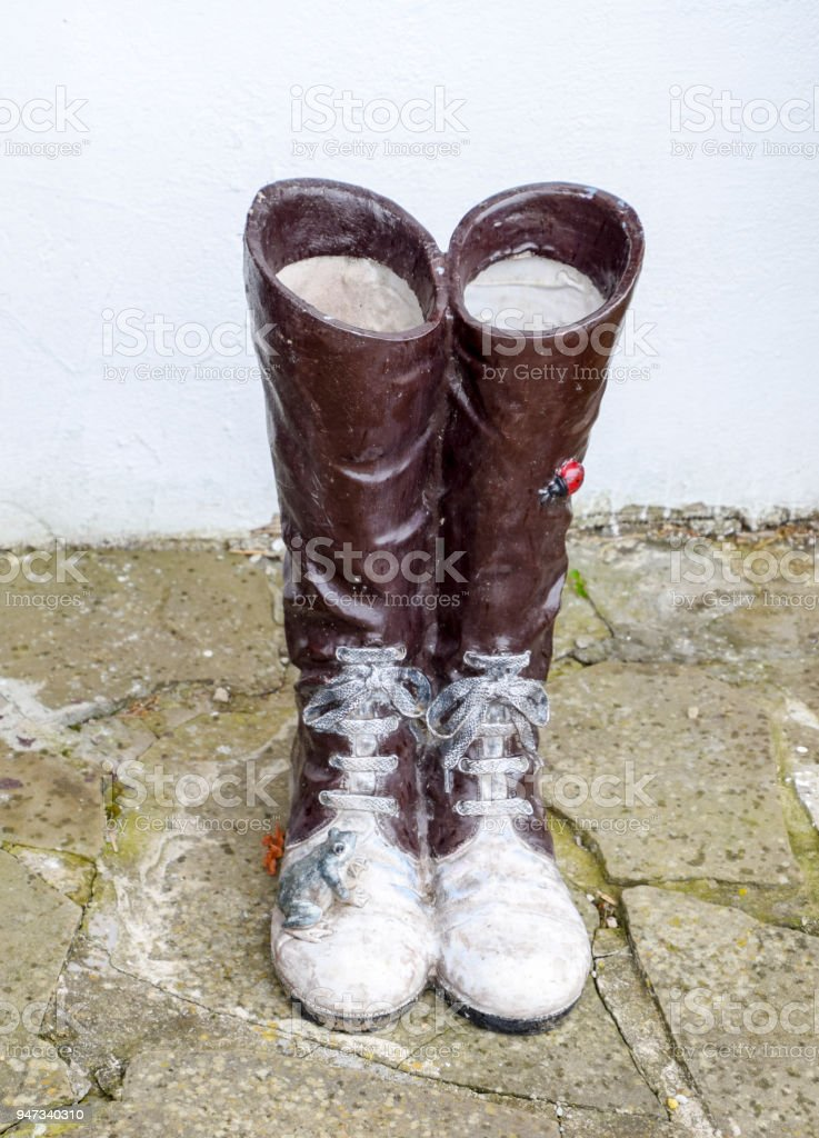 statue of boots with laces. A frog and a ladybug are sitting on the boots. stock photo
