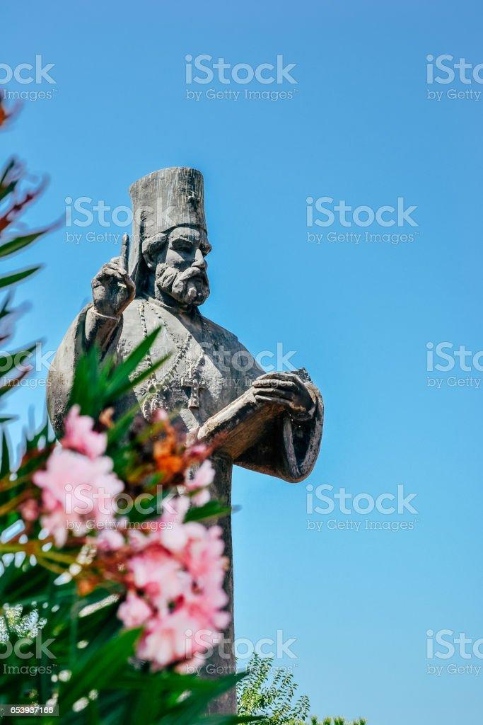 Statue of catholic orthodox priest in Podgorica, Montenegro. Pink flowers in foreground. stock photo
