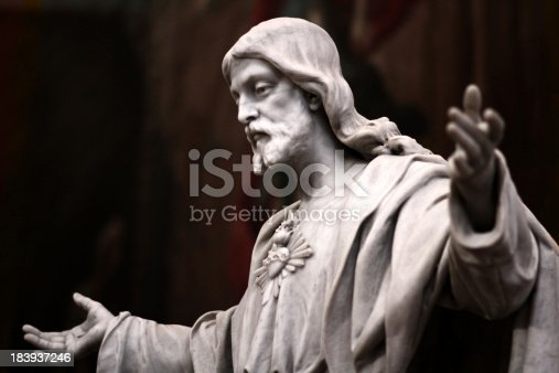An old statue of Jesus with his arms wide open.