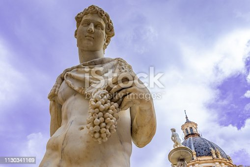 White stone Statue of Dionysus or Bacchus with bunch of grapes