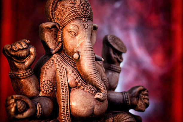 a statue of ganesha, a deity of india on red background - hinduism stock photos and pictures