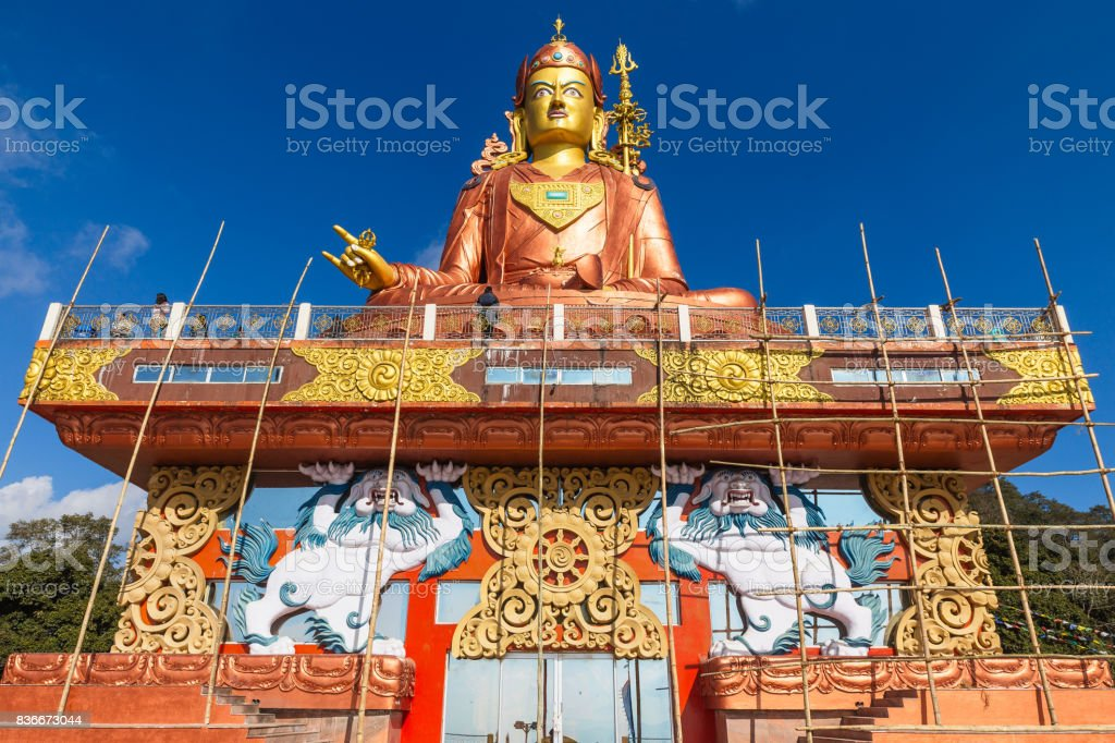 Statue of Guru Rinpoche, the patron saint of Sikkim that view at the base from front and  below with construction site in Guru Rinpoche Temple at Namchi. Sikkim, India. stock photo