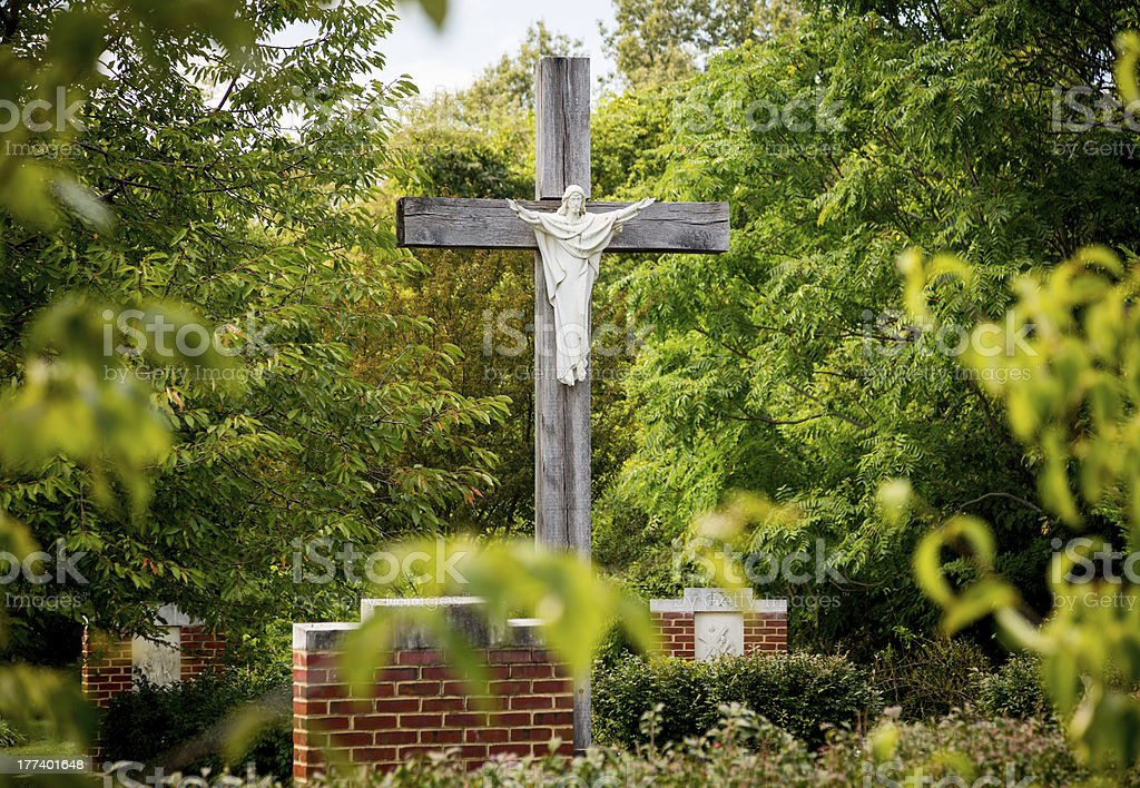 Statue of Jesus on cross in wooded garden stock photo