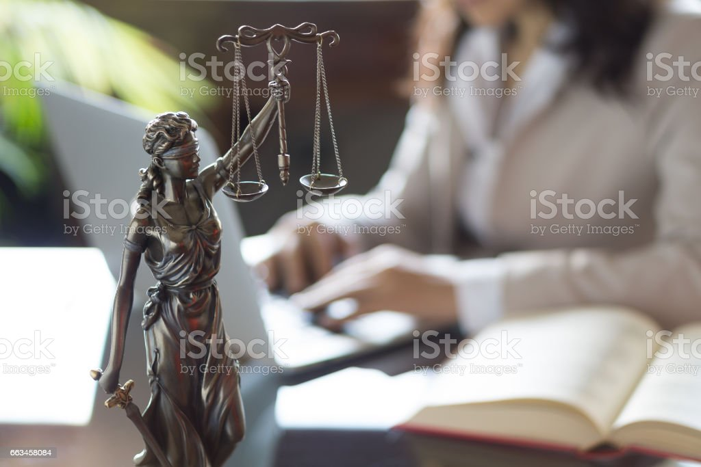 Statue of Justice and lawyer working on a laptop stock photo