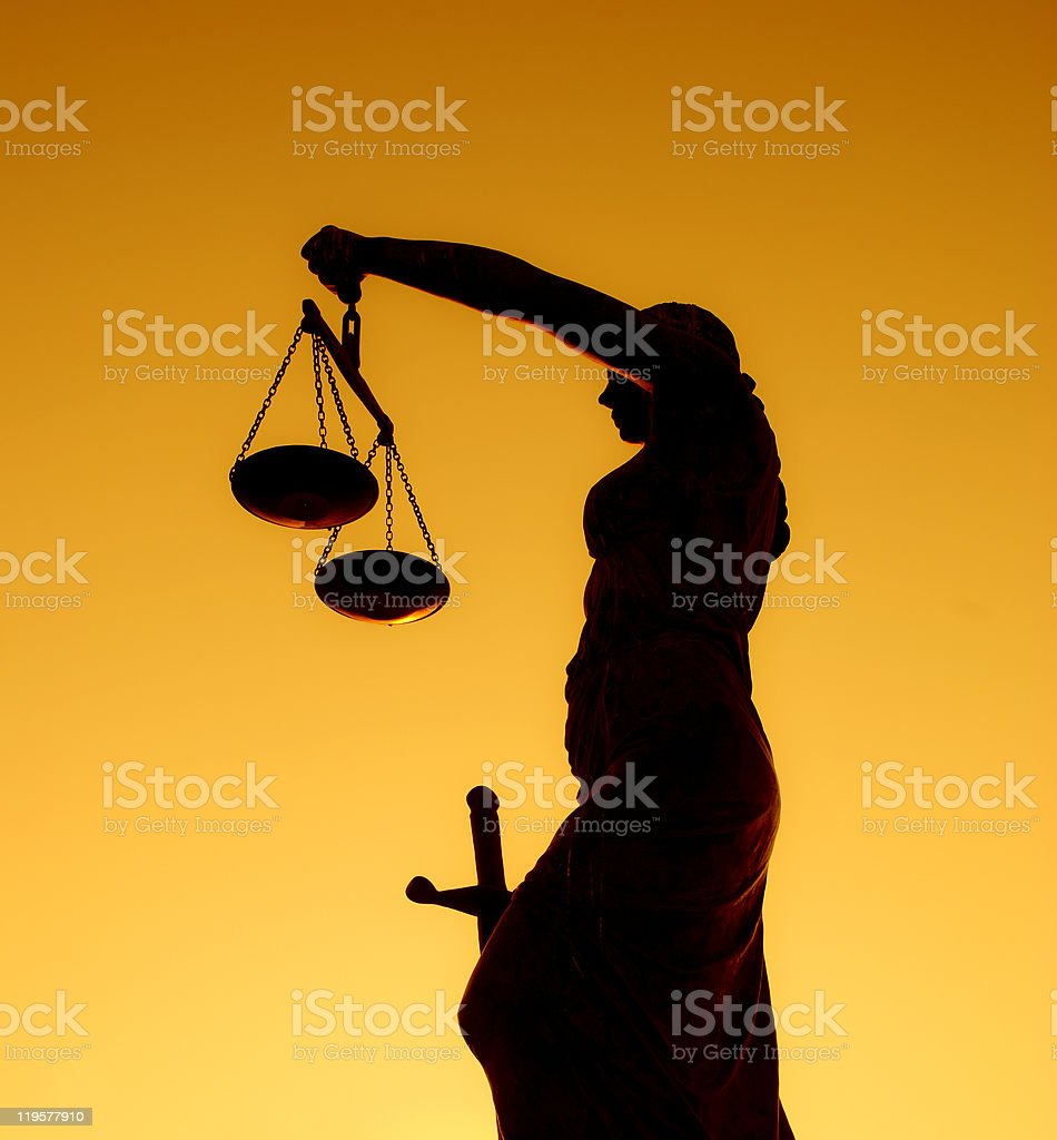 Statue of justice holding the scales in the sunset royalty-free stock photo