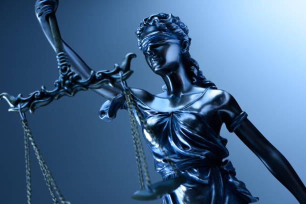 Statue of justice on blue background stock photo