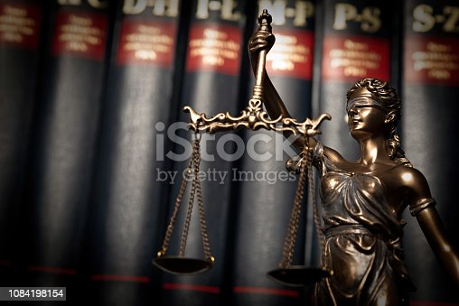 istock Statue of justice on books background 1084198154