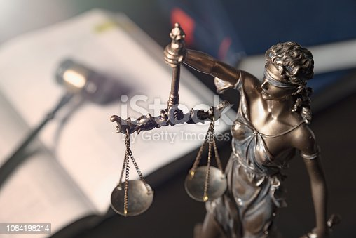 istock Statue of justice on books background 1084198214