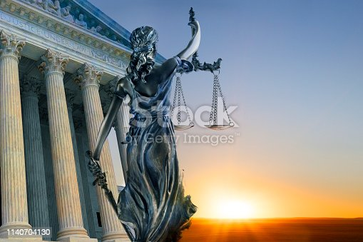 A statue of the blindfolded lady justice in front of the United States Supreme Court building as the sun rises in the distance symbolizing the dawning of a new era.