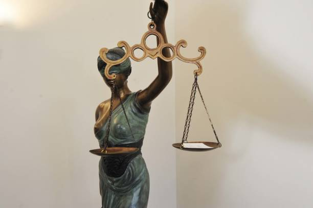 Statue of Lady Justice in court room Statue of Lady Justice with scales in her hand in a court room arbitrary stock pictures, royalty-free photos & images