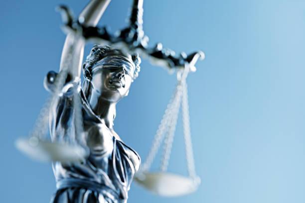 statue der justitia im vorderen blauen hintergrund - waage der gerechtigkeit stock-fotos und bilder