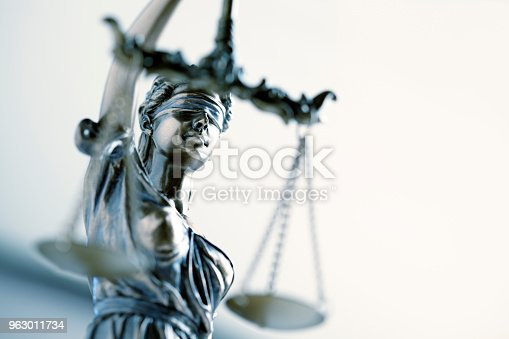 A close up and a low angle view of a statue of lady justice.  The image is photographed with a very shallow depth of field with the focus being on her face.