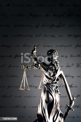 istock Statue of lady justice in front of a handwritten document. 1060802986