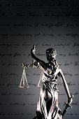 Statue of lady justice in front of a handwritten document.