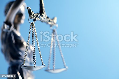 A close up and a low angle view of a statue of lady justice as it sits in front of a blue background  The image is photographed with a very shallow depth of field with the focus being on the justice scale.