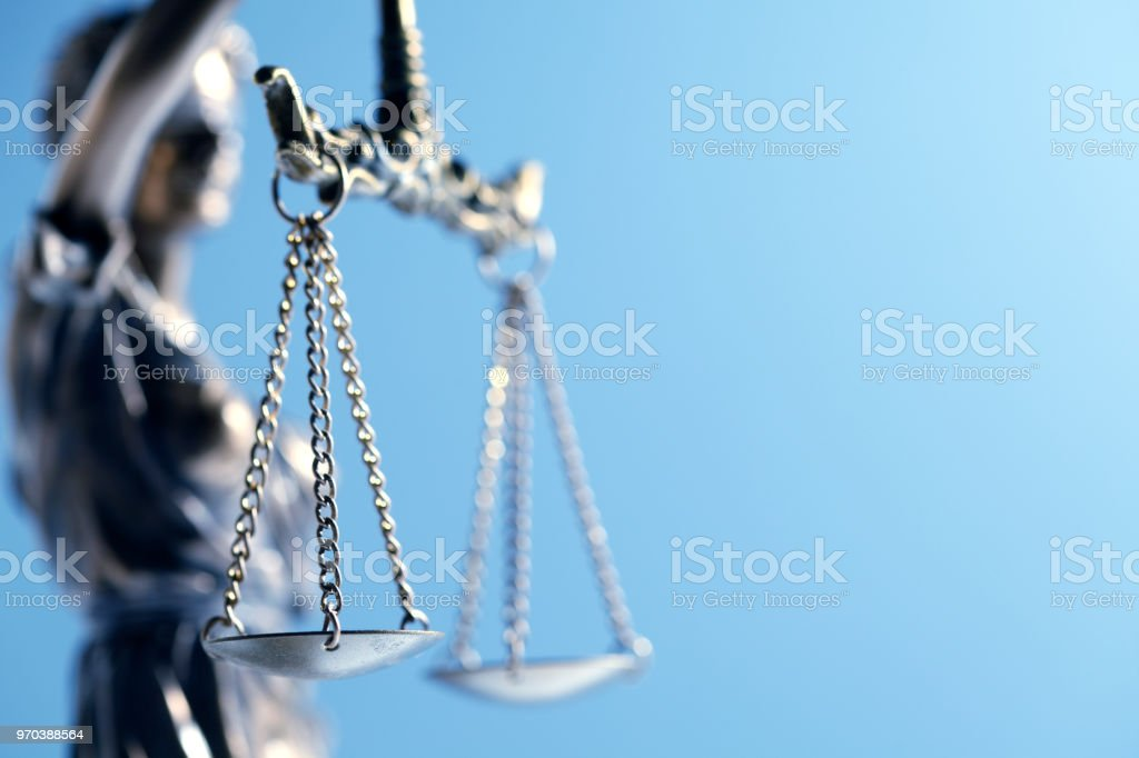 Statue Of Lady Justice In Front Of Blue Background stock photo