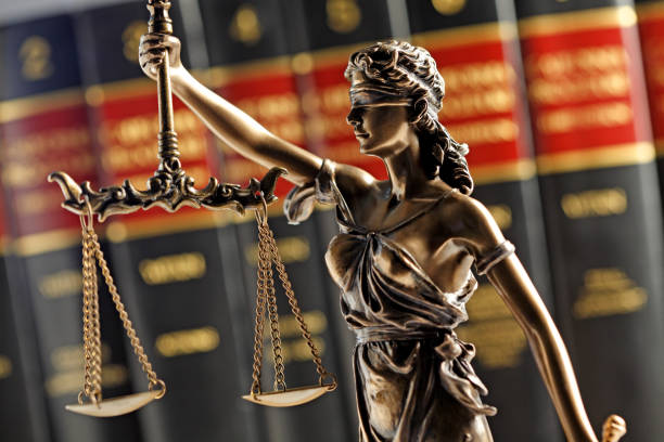 Statue Of Lady Justice In Front Of Row Of Law Books stock photo