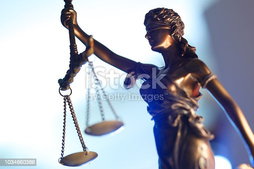 A statue of lady justice against a light blue background.