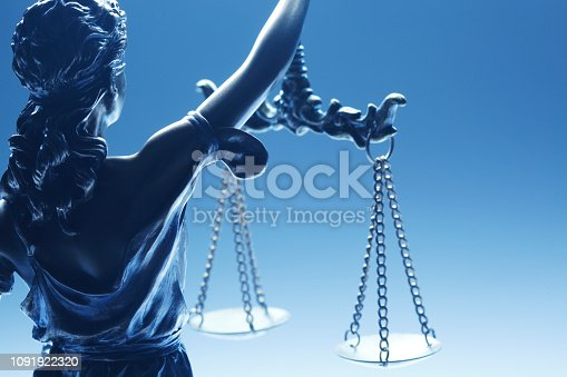 A close up of a statue of the blindfolded lady justice photographed with a very shallow depth of field.