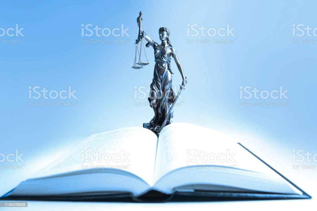 Statue Of Lady Justice Stands Over Open Law Book stock photo