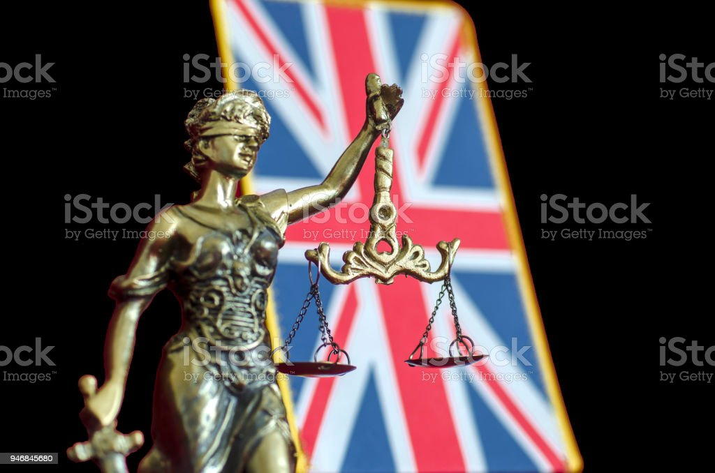 Statue of Lady Justice with United Kingdom flag stock photo