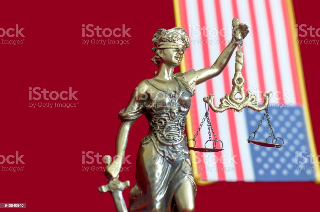 Statue of Lady Justice with United States of America flag stock photo