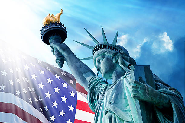 Statue Of Liberty And American Flag Under Blue Sky stock photo