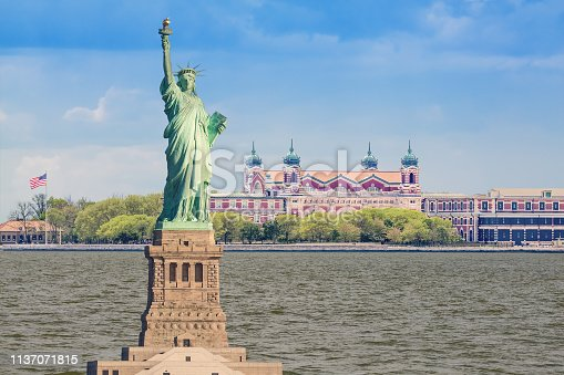 Statue of Liberty and Ellis Island, New York, USA. Water of New York Harbor and Blue Sky are in this HDR image.