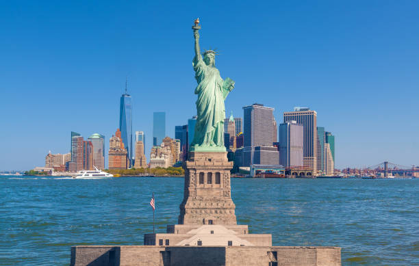 Statue of Liberty and New York City Skyline with Manhattan Financial District, World Trade Center, Water of New York Harbor, Battery Park and Blue Sky. stock photo