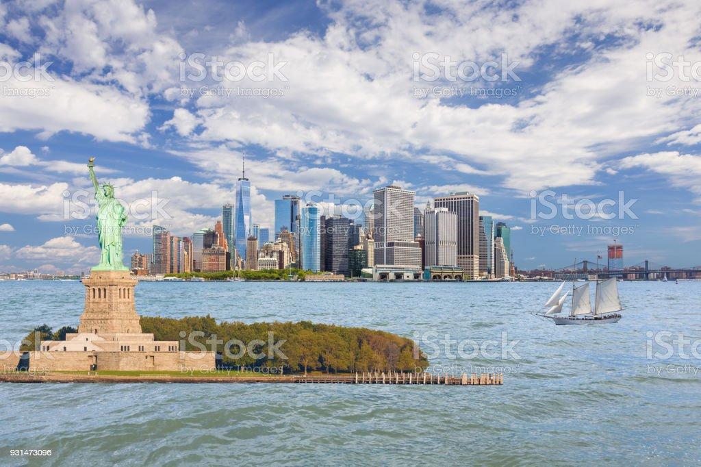 Statue of Liberty and New York City Skyline with Manhattan Financial District, World Trade Center, Sailboat (Tall Ship), Water of New York Harbor, Battery Park, Brooklyn Bridge, Manhattan Bridge and Blue Sky. stock photo