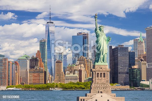 Statue of Liberty and New York City Skyline with Manhattan Financial District, Battery Park, Water of New York Harbor, World Trade Center, Tourboats and Blue Sky.