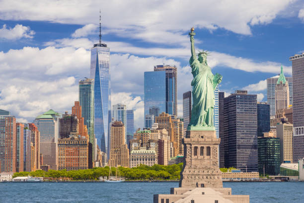 statue of liberty and new york city skyline with manhattan financial district, world trade center, water of new york harbor, battery park and blue sky. - international landmark stock photos and pictures