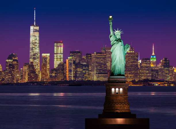 Statue of Liberty and New York City Skyline with World Trade Center and Manhattan Financial District at Sunset. stock photo
