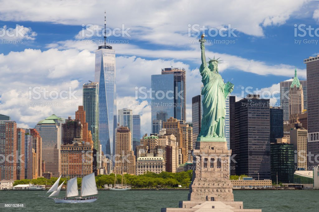 Statue of Liberty and New York Skyline with Manhattan Financial District and World Trade Center, Sailboat (Tall Ship), Water of New York Harbor and Blue Sky with Clouds. stock photo