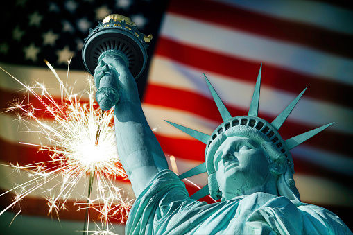182764873 istock photo Statue of Liberty and sparkler on American flag 496263807