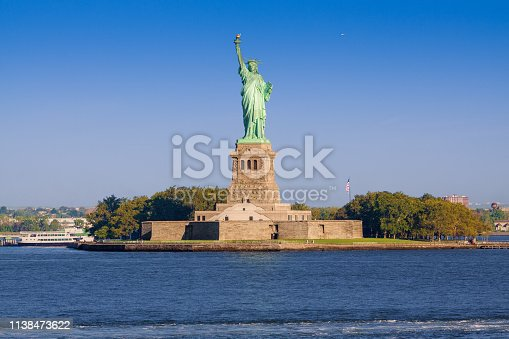 Statue of Liberty with Jersey City Skyline and Water of New York Harbor, NY, USA.