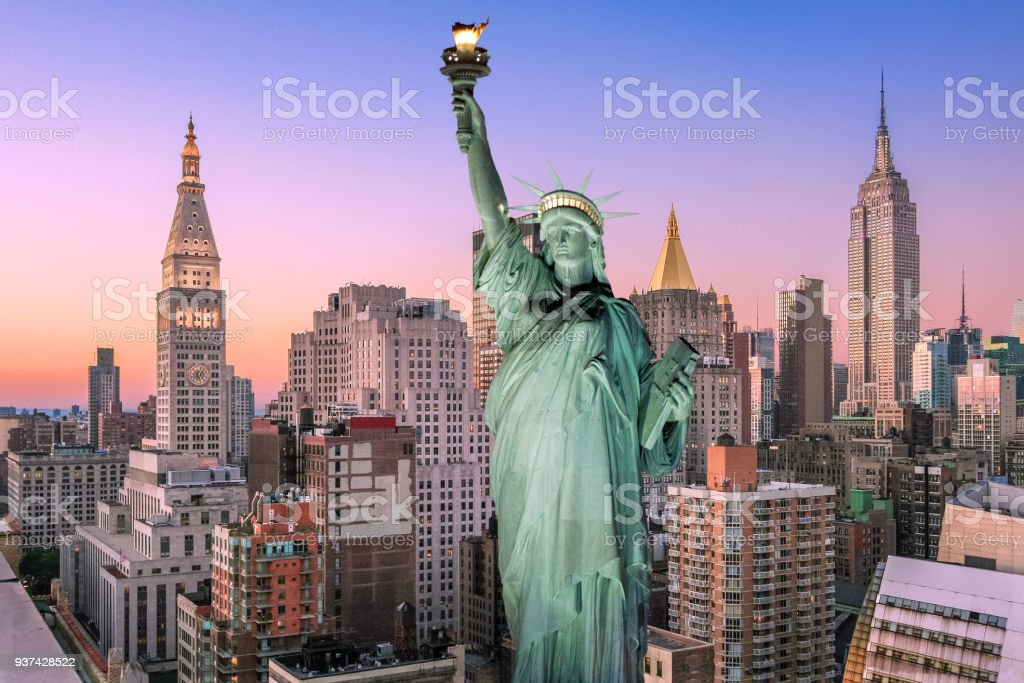 Statue of Liberty at Sunset and New York City Skyline with Empire State Building, Metropolitan Life Insurance Company Tower, Midtown Manhattan Skyscrapers and Orange-Blue Clear Sky. stock photo
