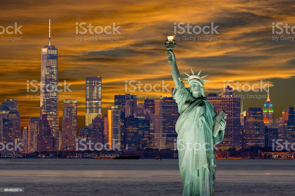 Statue of Liberty at Sunset with New York City Skyline, Manhattan Financial District, World Trade Center, Empire State Building and Dramatic Sky. royalty-free stock photo