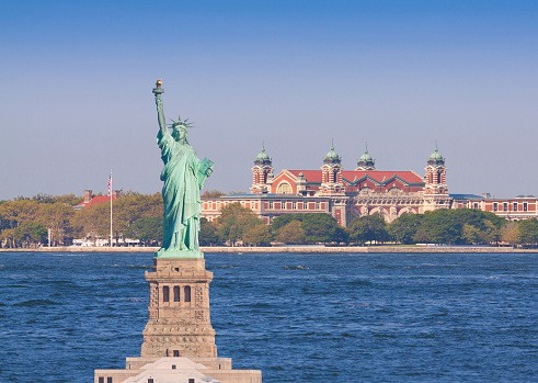 Statue of Liberty, lit by morning sun, with Ellis Island in background, New York City. More than 12 million immigrants entered America through the golden door of Ellis Island. Canon EF 70-200mm f/4L IS lens.