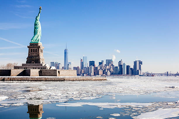 Statue of Liberty NYC Skyline Frozen Hudson River Brooklyn Bridge Ice sheets form around Statue of Liberty and NYC. One World Trade Center. Brooklyn Bridge, right. Hudson river freezes over from arctic weather. lower manhattan stock pictures, royalty-free photos & images