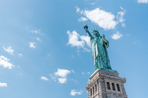 Statue of Liberty on sunny day, clear blue sky background. United States nation symbol, travel destination or America tourist attraction concept