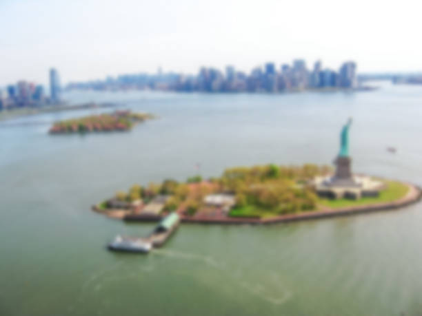 Statue of Liberty panorama Defocused background with helicopter view of Liberty Island and the famous Statue of Liberty monument symbol of New York City, United States.  Intentionally blurred post production for bokeh effect. liberty island stock pictures, royalty-free photos & images