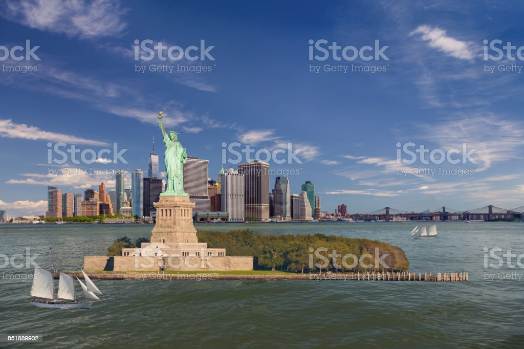 Statue of Liberty, Sailboat (Tall Ship), Water of New York Harbor, Skyline with Manhattan Financial District and World Trade Center, Brooklyn Bridge and Blue Sky, New York City. stock photo