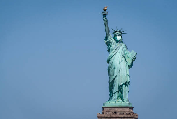 statue of liberty wearing a surgical mask - демократия стоковые фото и изображения
