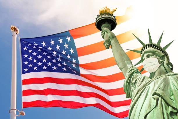 Freiheitsstatue trägt eine chirurgische Maske, US-amerikanische Flagge Hintergrund. Neues Coronavirus, covid-19 in New York und USA Seuchenkrisenkonzept – Foto